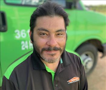 male Project Manager in front of green truck